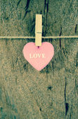 Lovely pink hearts hanging on the clothesline on old wood backgr — Zdjęcie stockowe