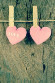 Lovely pink hearts hanging on the clothesline on old wood backgr — Stock Photo