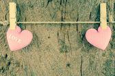Lovely pink hearts hanging on the clothesline on old wood backgr — Stok fotoğraf