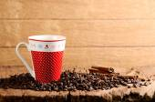 Coffee cup on wooden table and Roasted coffee beans around — Stock Photo
