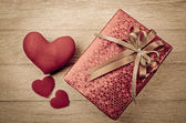 Red gift box on wood background — Stock Photo
