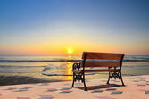 Bench near the beach and clear blue sky — Stock Photo