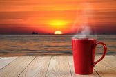 Red coffee cup with smoke on sun rise background — Stock Photo