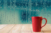Red coffee cup with natural water drops on glass window background — Stock Photo