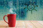Red coffee cup with smoke and sun sign on water drops glass wind — Stock Photo