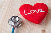 Stethoscope with red heart on wooden background — Stock Photo
