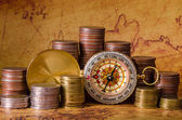 Compass and stack of coins on old map — Stock Photo