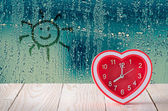 Red clock on rain drop and sun sign glass window background — Stock Photo