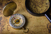 Compass and magnifying glass on old map — Stock Photo