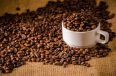 Coffee cup and coffee beans around — Stock Photo