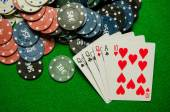 Playing cards 'Three of a kind' and chips on green background — Stock Photo