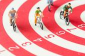 Miniature people cycling on darts — Stock Photo