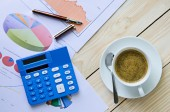 Coffee cup and business graph on wooden table — Stock Photo
