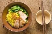 Yellow noodles served with sliced pork — Stock Photo