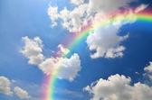 Arco-íris e nuvens brancas em fundo azul céu — Fotografia Stock