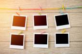 Empty black photo frames hanging with clothespins on wooden back — Stock Photo