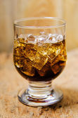 Glass of cola with ice cubes on wooden background — Stock Photo