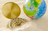 Compass and world model on sea sand — Stock Photo