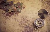 Vintage compass and coins on old map — Stock Photo