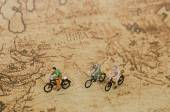Miniature people ride bicycle on vintage map — Stock Photo