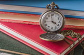 Pocket or pendant watch on background of old books — Stock Photo