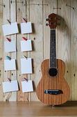 Ukulele guitar with blank photo frame background — Stock Photo