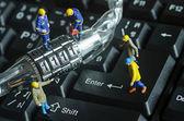 Miniature people try to unlock metal security lock key — Stock Photo
