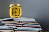 Alarmklocka på högen med öppen bok — Stockfoto