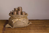 Bags filled with coins on wooden table — Stock Photo