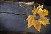 Autumn yellow leaf with with heartover wooden backgound — Stock Photo