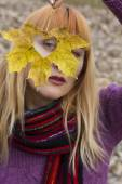 Woman looking through autumn leaf with heart shaped hole — Stock Photo