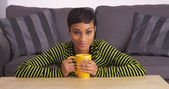 African woman smiling at coffee table with mug — 图库照片
