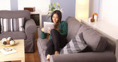 Japanese woman sitting on couch with tablet — Stock Photo