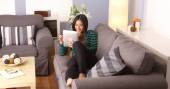 Asian woman sitting on couch with tablet computer — Stock Photo