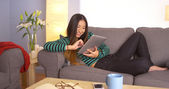 Cute Japanese woman using tablet on couch — Stockfoto