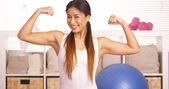 Strong Asian woman showing off muscles — Stock Photo