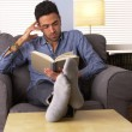 Постер, плакат: Attractive Latino reading a book at home