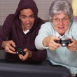 Mexican guy playing video games with grandma — Stock Photo #57323643