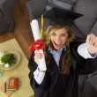 Female graduate celebrating with diploma — Stock Photo #57329365