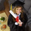 Female College graduate holding diploma and smiling — Stock Photo #57329385