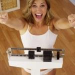 Happy woman celebrating weight loss — Stock Photo #57329461