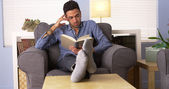 Attractive Latino reading a book at home — Stock Photo