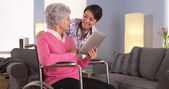 Asian woman and Elderly patient talking with tablet — Stock Photo