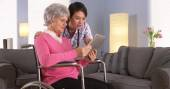 Elderly patient and Asian nurse talking with tablet — Stockfoto