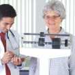 Mexican doctor weighing elderly patient — Stock Photo #57341799
