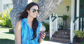 Mixed race woman standing by tree drinking iced tea — Stock Photo