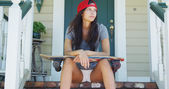 Young woman sitting on porch with skateboard — Foto de Stock