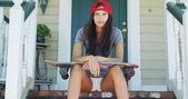 Giovane donna che si siede sul portico con il pattino — Foto Stock