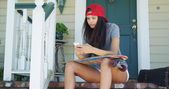 Mixed race woman sitting on porch with skateboard texting — Foto de Stock