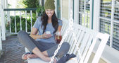 Young woman texting and sitting on porch — Stock Photo